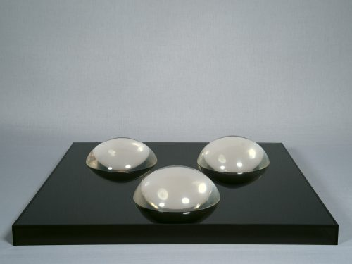 Judy Chicago<br> <i>Clear Domes on Dark Base,</i> 1968<br> Clear acrylic domes on mirrored glass on Plexiglas base<br> 3 domes, each 3.5 x 8.94 inches / 8.9 x 22.6 cm Total 5.5 x 30.5 x 30.5 inches / 14 x 77.5 x 77.5 cm