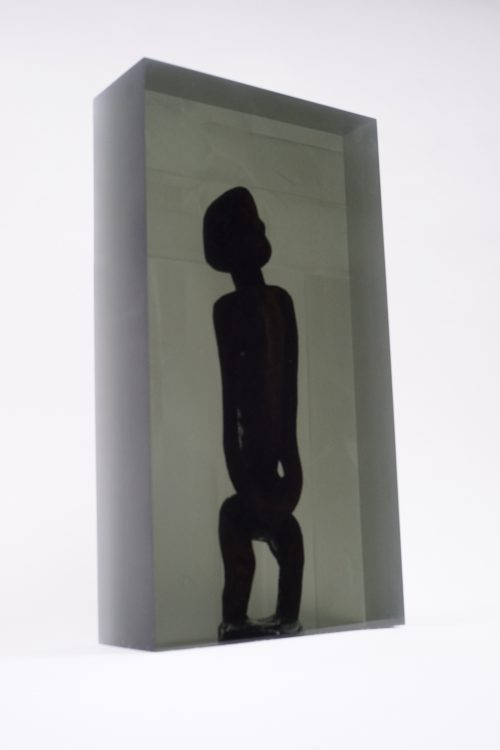 Matthew Angelo Harrison<br> <i>Dark Silhouette: Timid Male Figure,</i> 2018<br> Wooden sculpture from West Africa, polyurethane resin, anodized aluminum<br> Overall: 66 1/8 x 13 x 13 inches / 168 x 33 x 33 cm<br> Sculpture: 17 5/8 x 3 3/4 x 9 3/4 inches / 44.8 x 9.5 x 24.8 cm