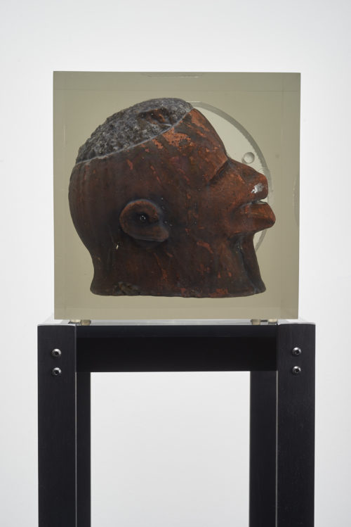 Matthew Angelo Harrison<br>  <em>Dark Silhouette: Angled Gaze</em>, 2018<br>  Wooden sculpture from West Africa, polyurethane resin, anodized aluminum, acrylic<br>  50 x 13 3/4 x 9 1/4 inches / 127 x 34.9 x 23.5 cm