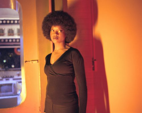 Isaac Julien<br><em>Baltimore Series (Angela in Orange) </em>, 2003<br>Framed archival pigment print on Epson Premium Photo Glossy 250gsm paper mounted on aluminum<br>43 3/4 x 54 3/8 inches / 111.2 x 138 cm